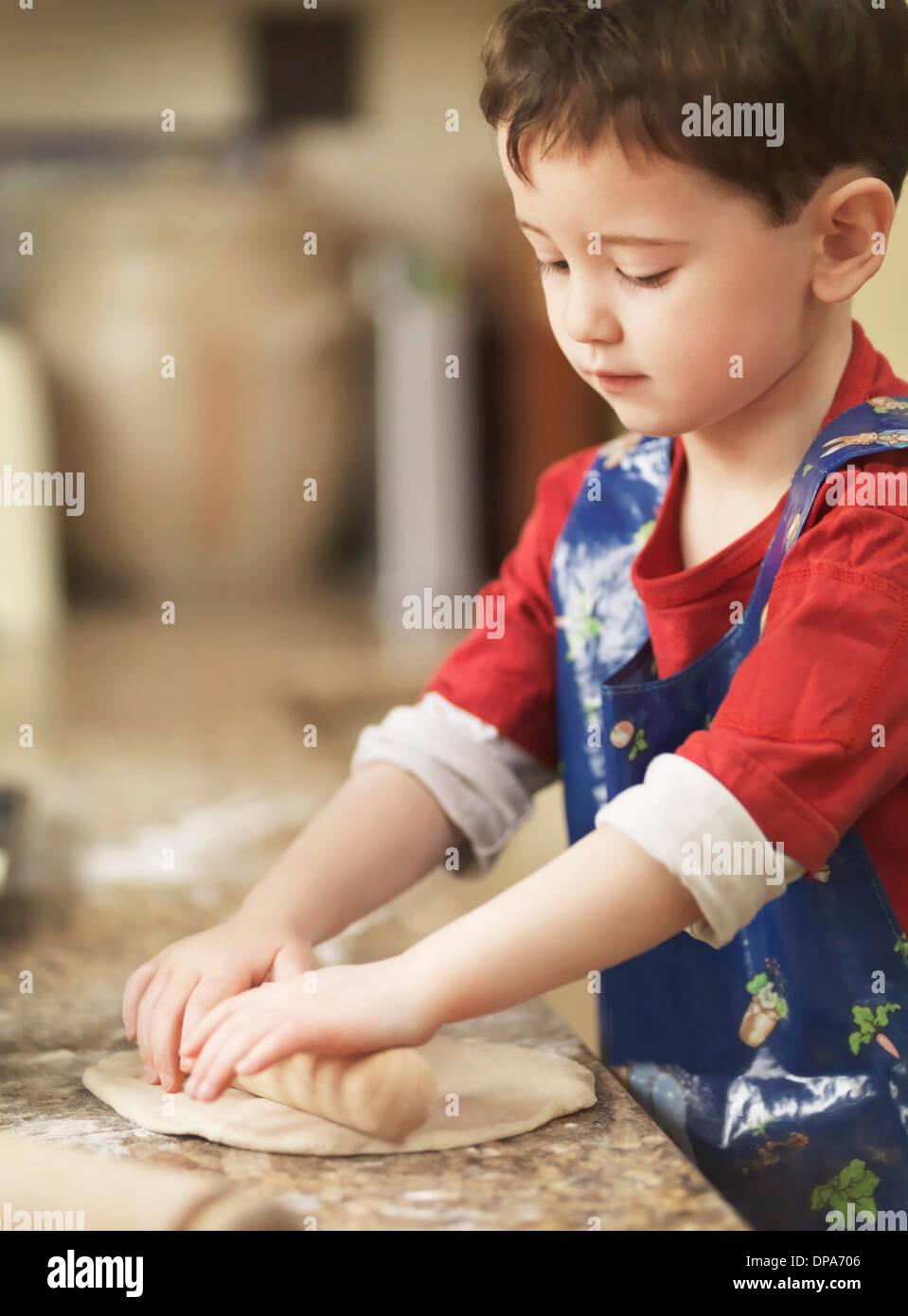 Kind kneten Teig mit Nudelholz Stockbild