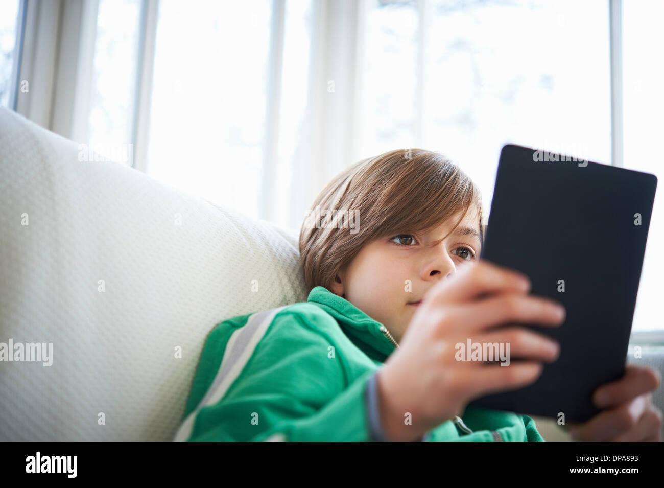 Junge auf Sofa mit digital-Tablette Stockfoto