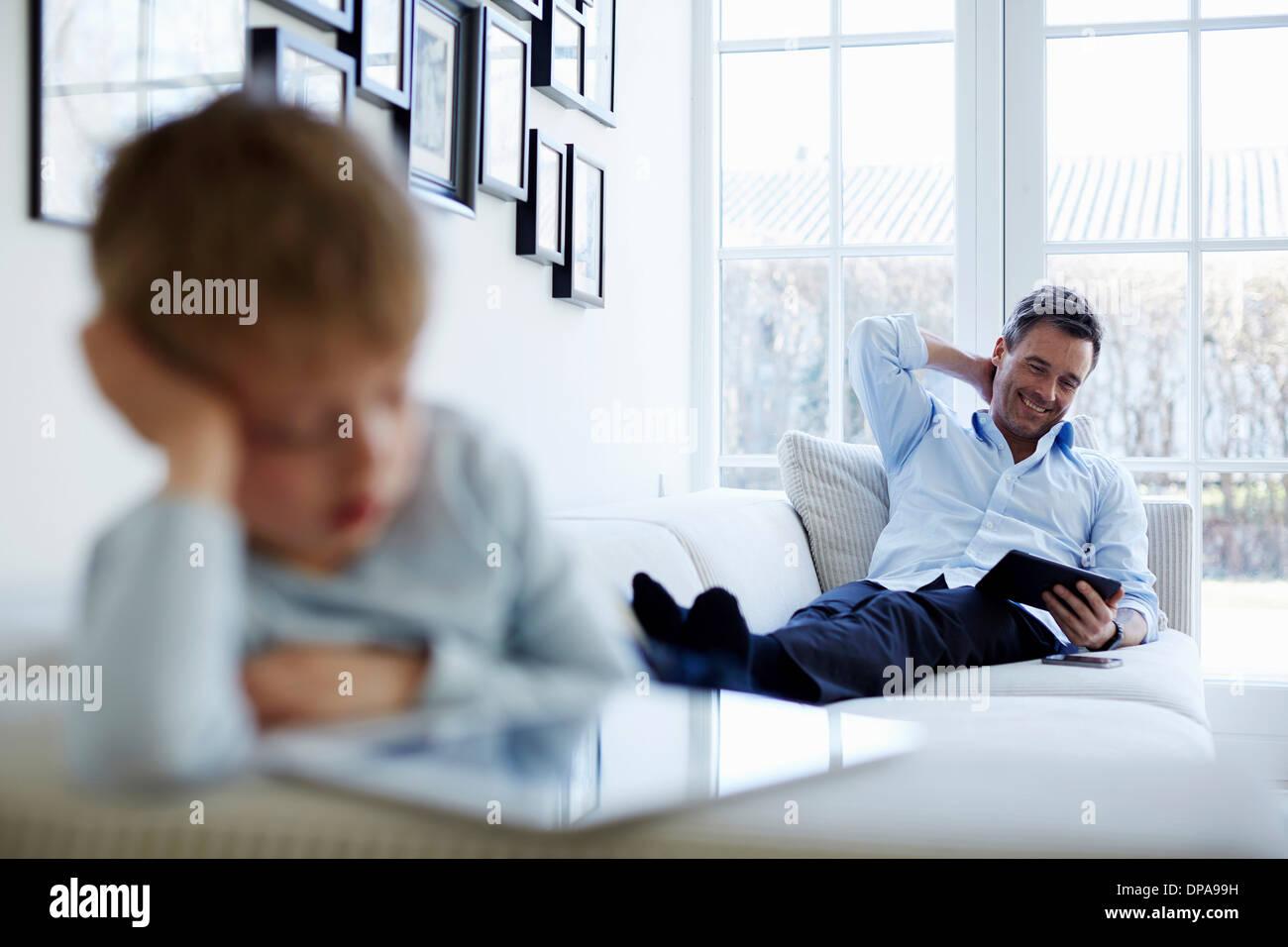 Vater und Sohn sitzen auf Sofa mit digitalen Tabletten Stockfoto