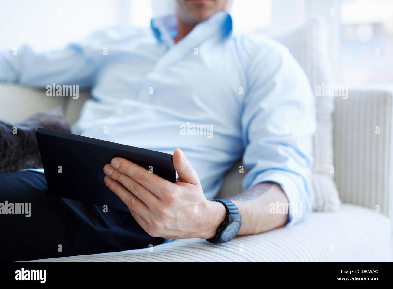 Schuss des Mannes Mittelteil hält digitale Tablet beschnitten Stockbild
