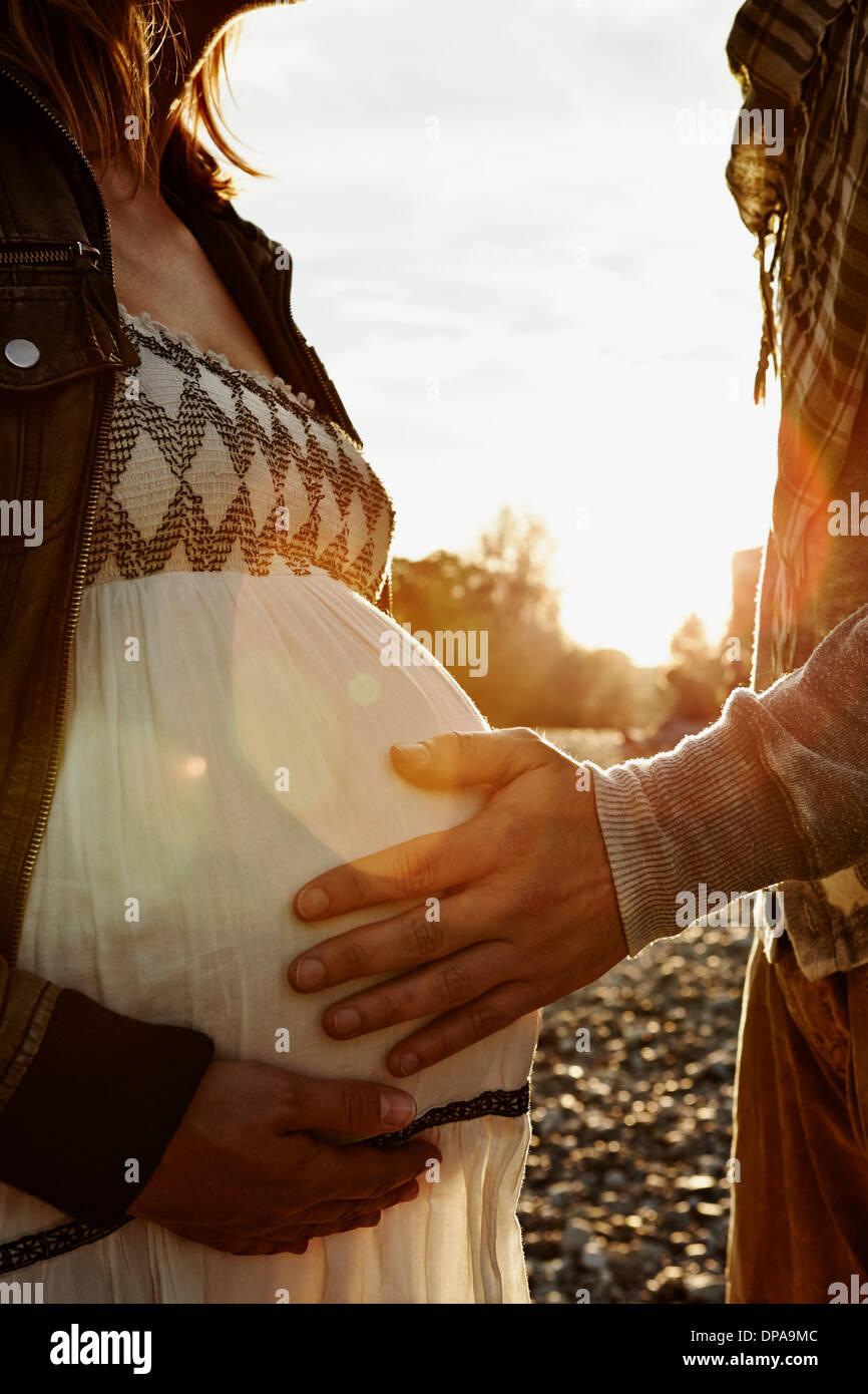 Mittelteil der schwangeren Frau und Partner berühren Beule Stockbild