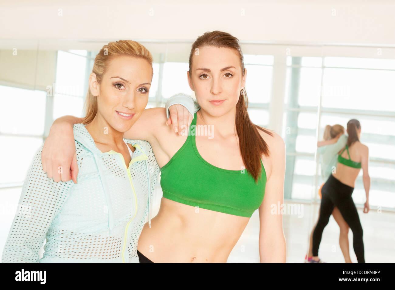 Frauen stehen im Fitnessraum mit Arm um Stockbild