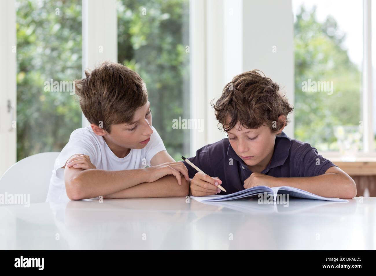 Brüder, die gemeinsam an Hausaufgaben Stockbild