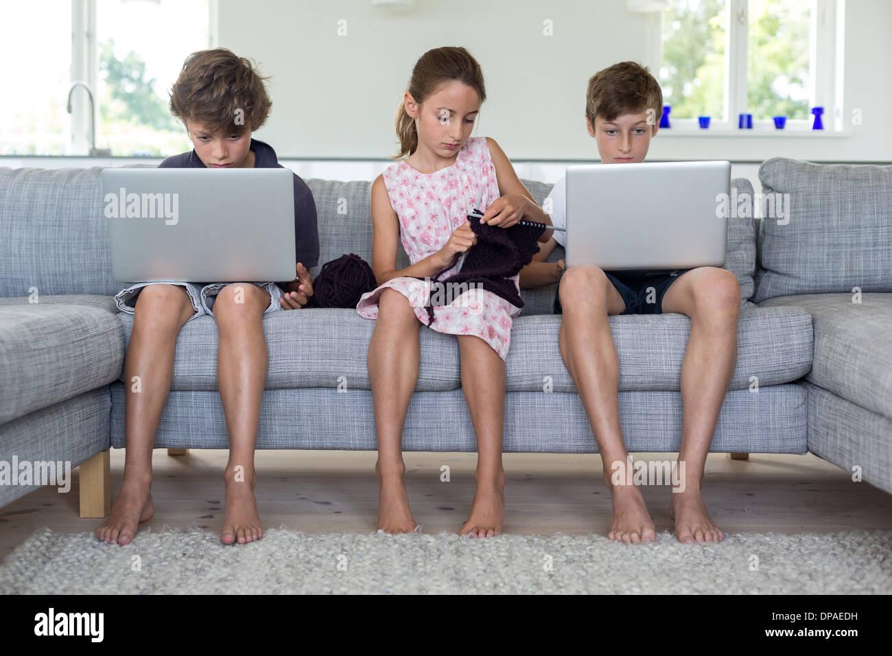 Brüder und Schwester auf Sofa mit Computern und stricken Stockfoto