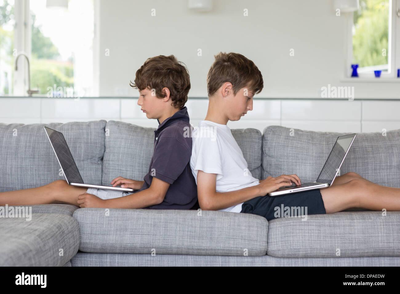 Brüder Rücken an Rücken auf Sofa mit Computern Stockbild