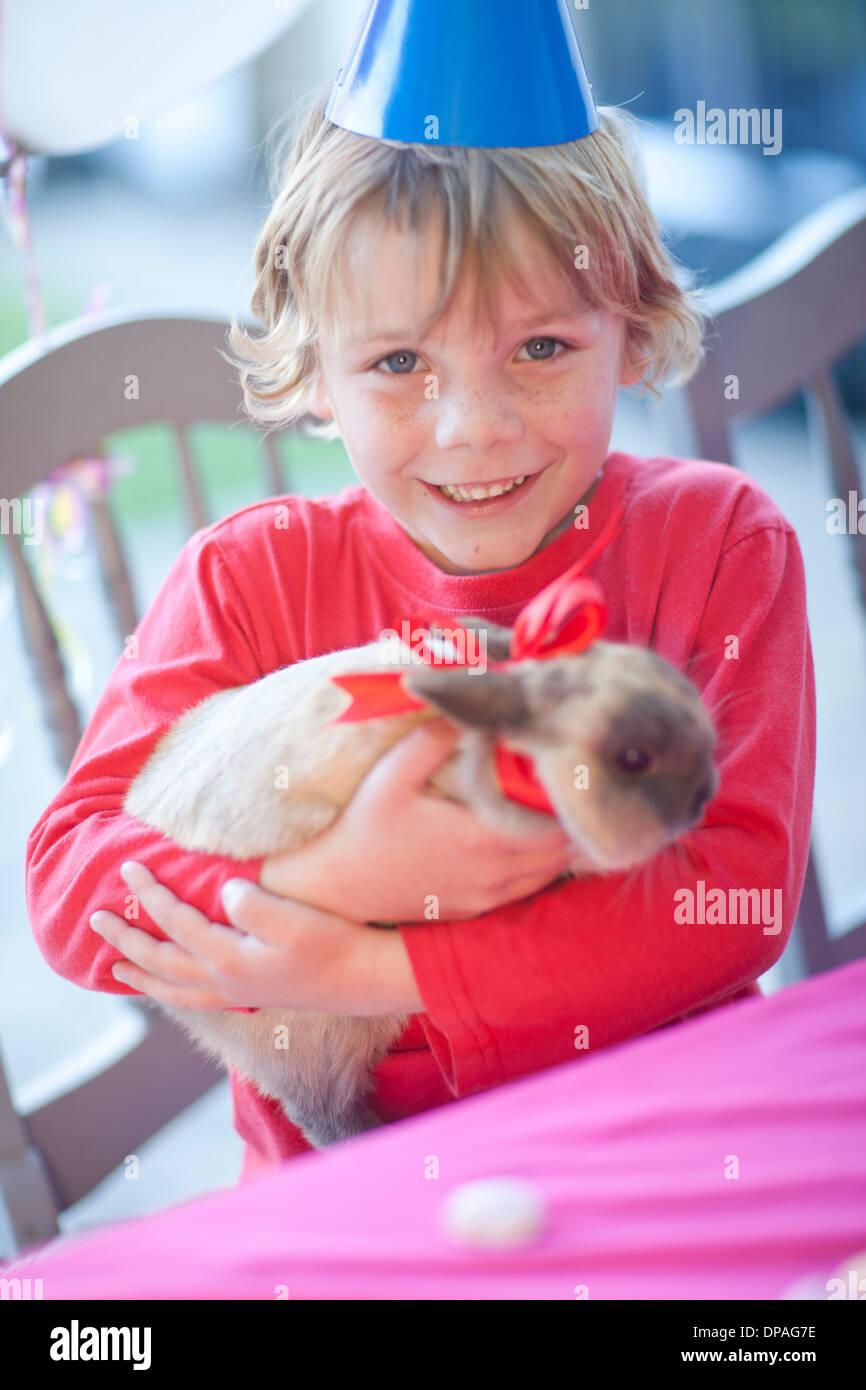 Junge Geburtstagskind umarmt seine Kaninchen Stockfoto