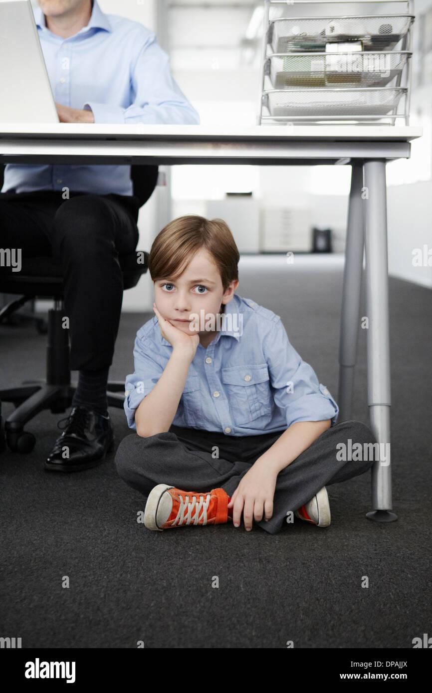 Junge sitzt auf Boden mit Geschäftsmann arbeiten am Schreibtisch Stockfoto
