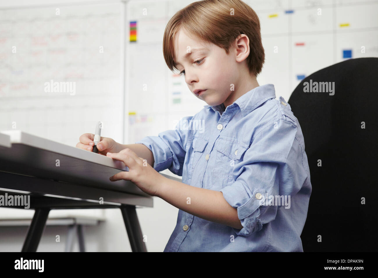 Junge schreiben am Schreibtisch im Büro Stockbild
