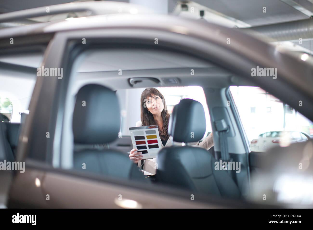 Mitte Erwachsene Frau mit Farbfeld im Autohaus Stockfoto