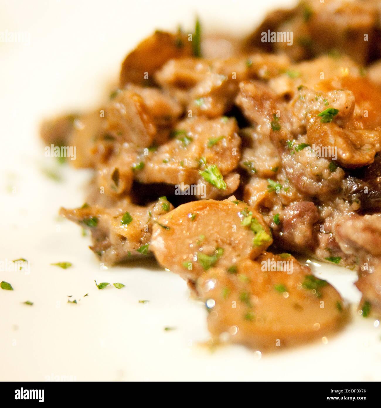 Rindergulasch mit Champignons und Petersilie. auf weißen Teller Stockbild