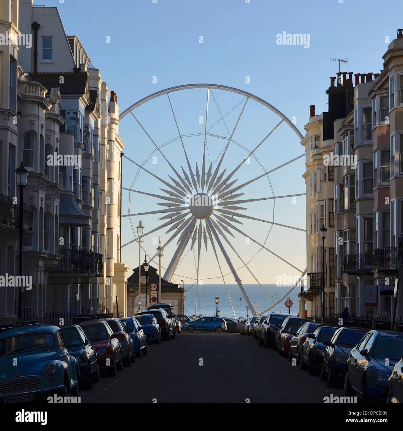 Brighton Wheel - Riesenrad von Kemp Town mit dem Meer im Hintergrund, umrahmt von viktorianischen Reihenhäusern Stadt betrachtet Stockbild