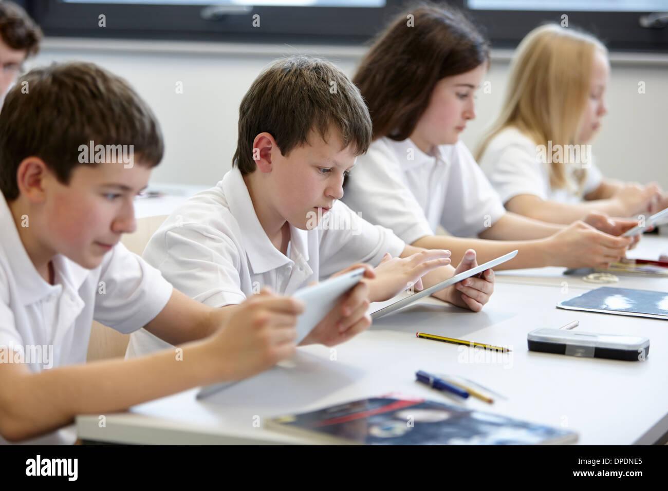 Zeile der Schülerinnen und Schüler arbeiten in der Klasse Stockbild