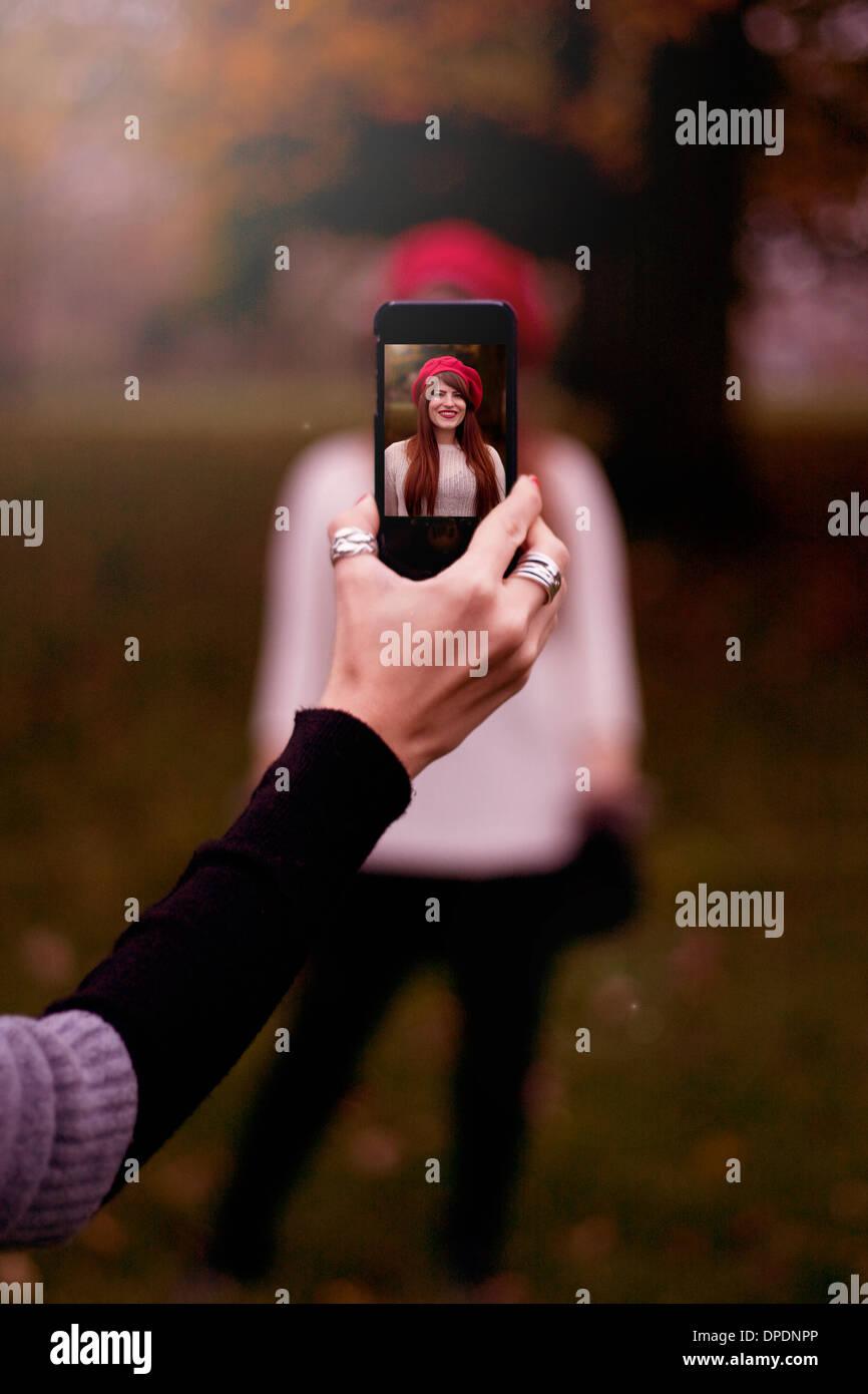 Hand mit Smartphone, Foto der jungen Frau Stockbild