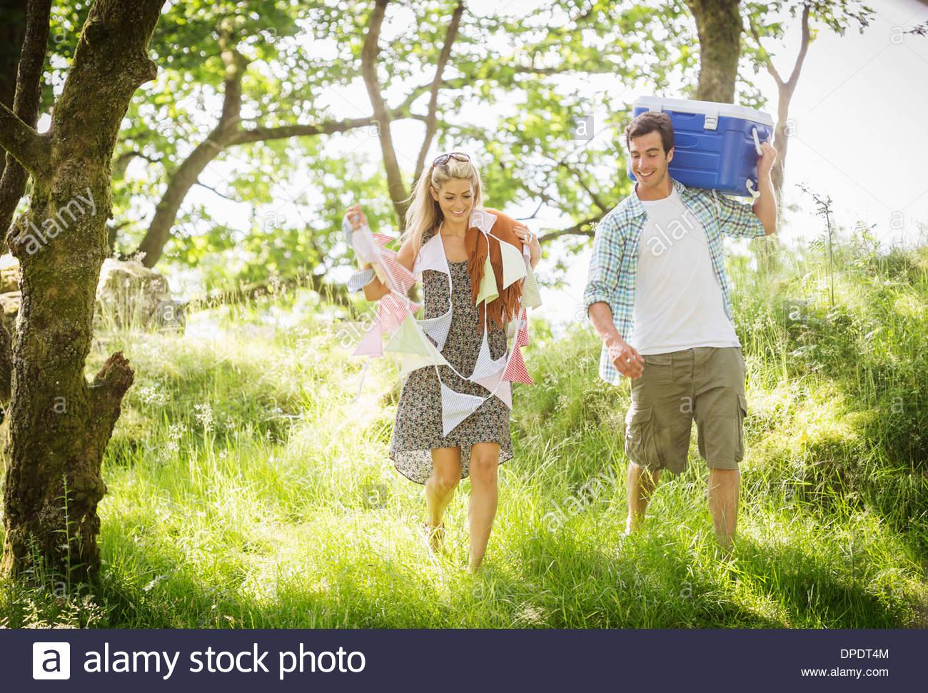 Junges Paar im Wald mit Girlanden und Kühlbox Stockbild
