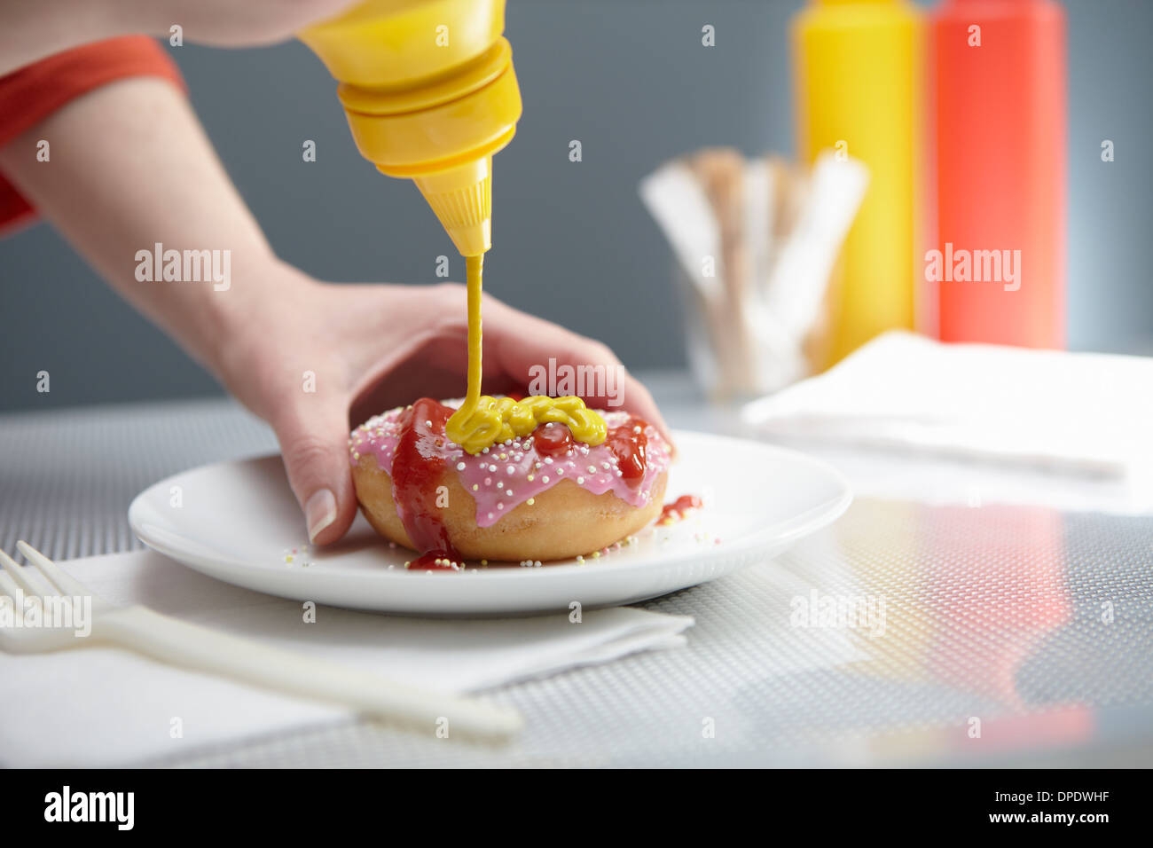 Frau spritzt Donut mit Ketchup und Senf Stockbild