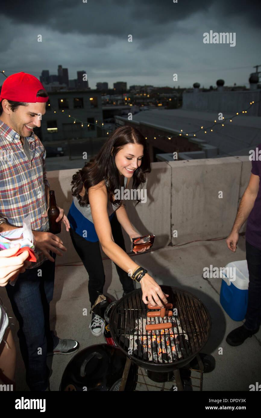 Junge Erwachsene Freunde Grillen auf Party auf dem Dach Stockbild