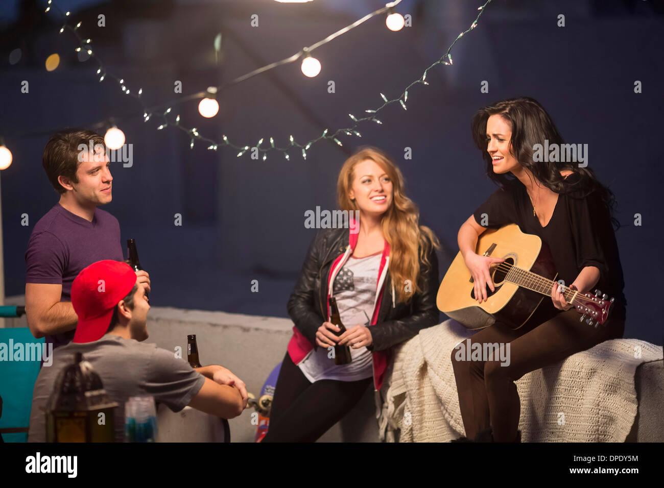 Junge Erwachsene Freunde anhören von Gitarre auf party Stockbild