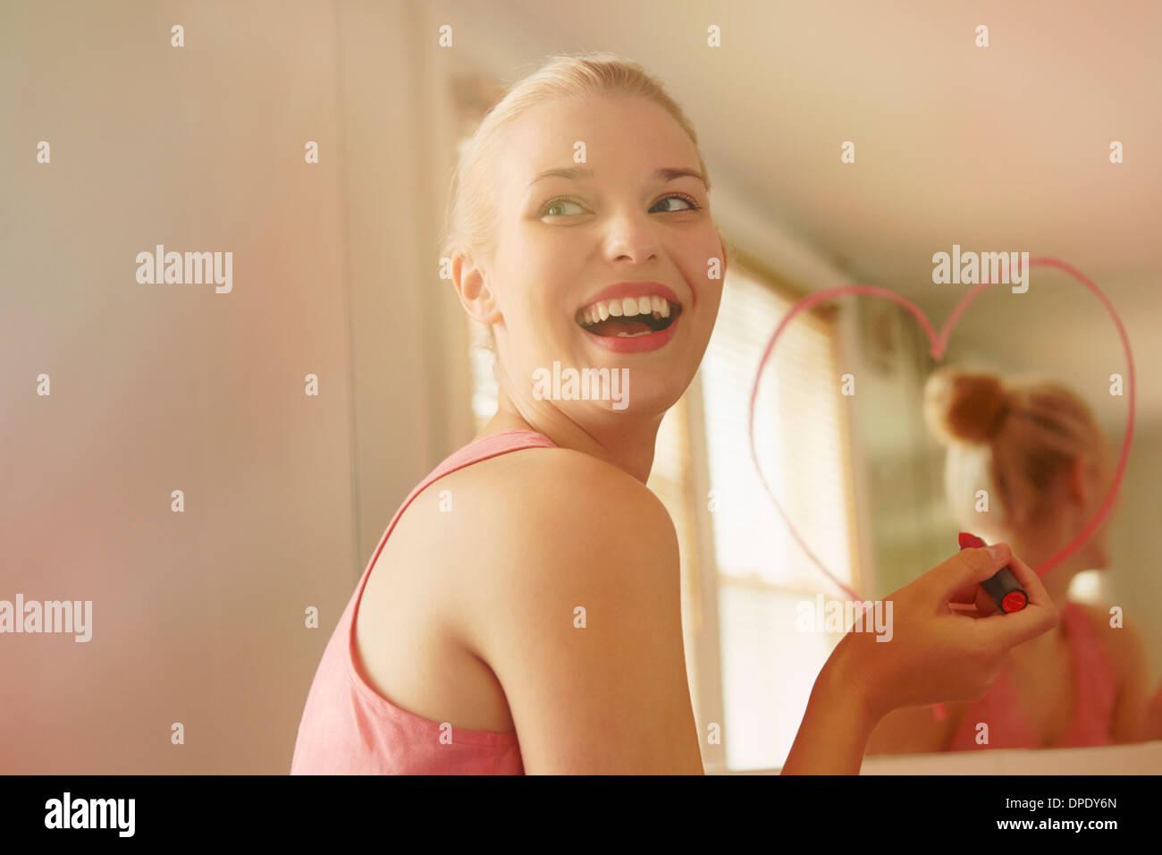 Junge Frau im Badezimmer Spiegel mit Lippenstift Herzform ausgehend Stockfoto