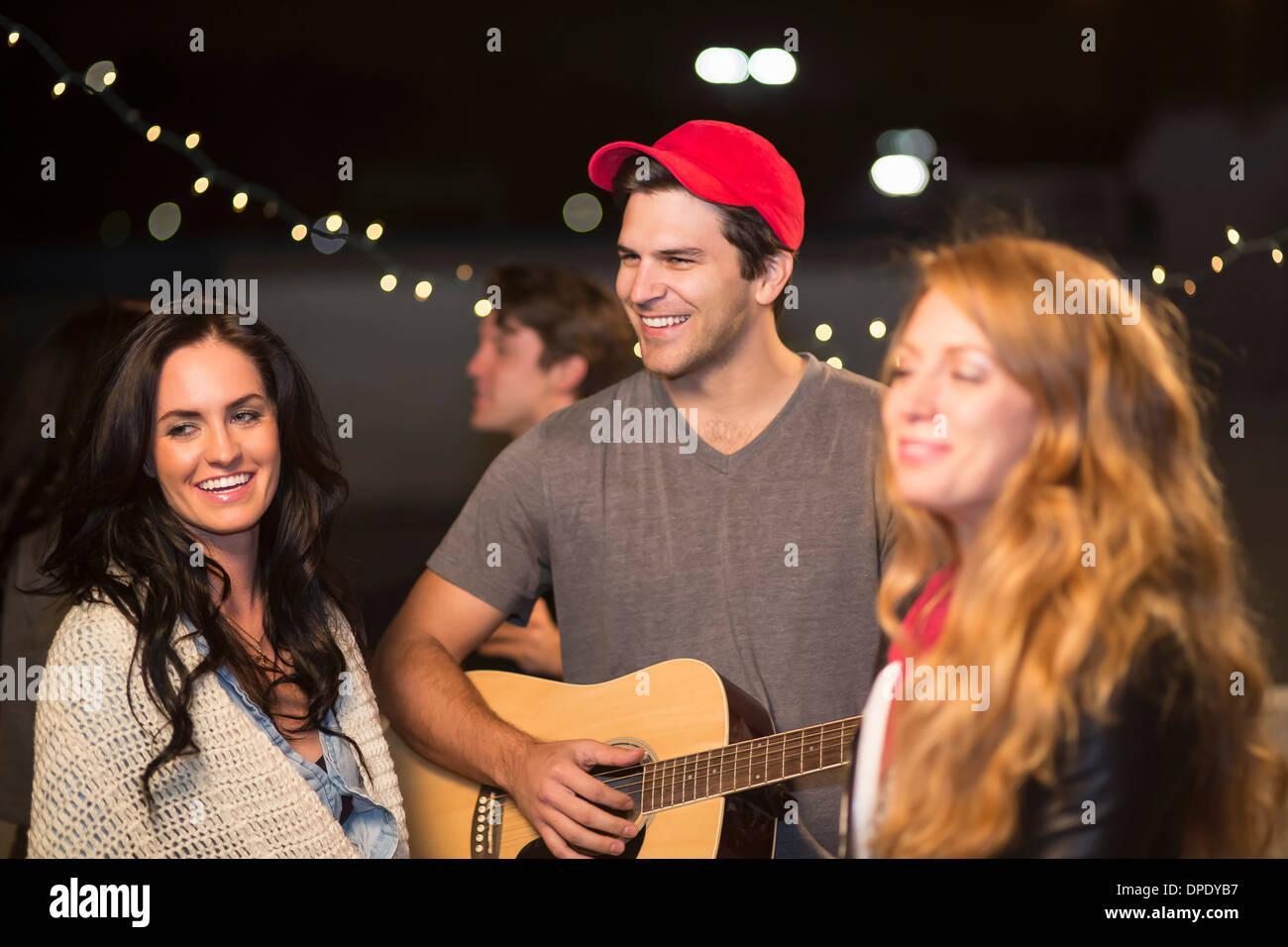 Junge Erwachsene Freunde genießen Gitarrenmusik auf Party auf dem Dach Stockbild