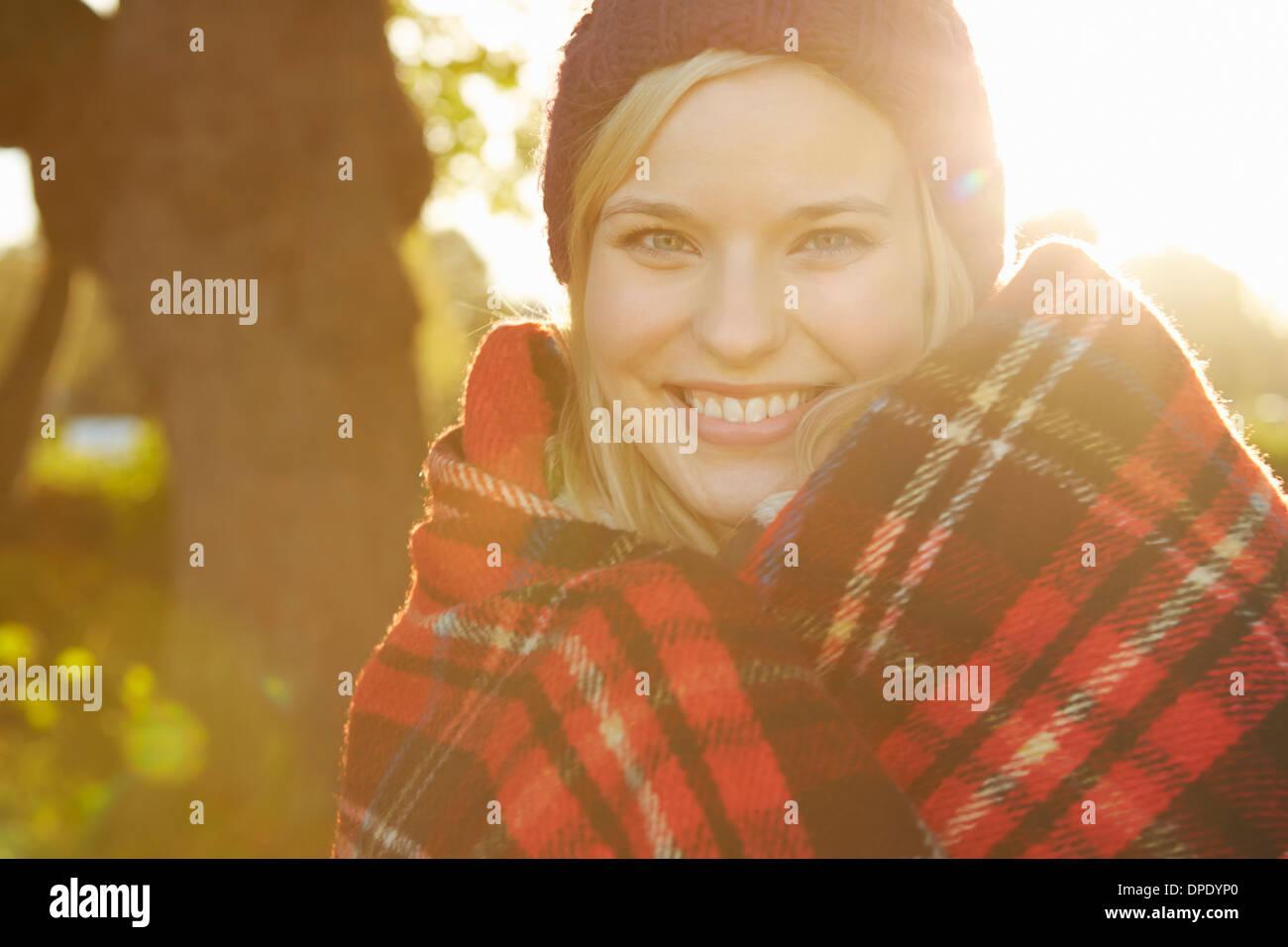 Porträt der jungen Frau im Park, Tartan Picknickdecke um Schultern Stockbild