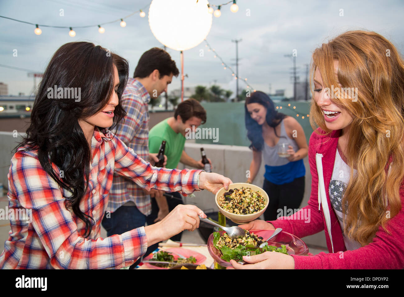 Junge Erwachsene Freunde genießen das Essen im Grill Stockbild