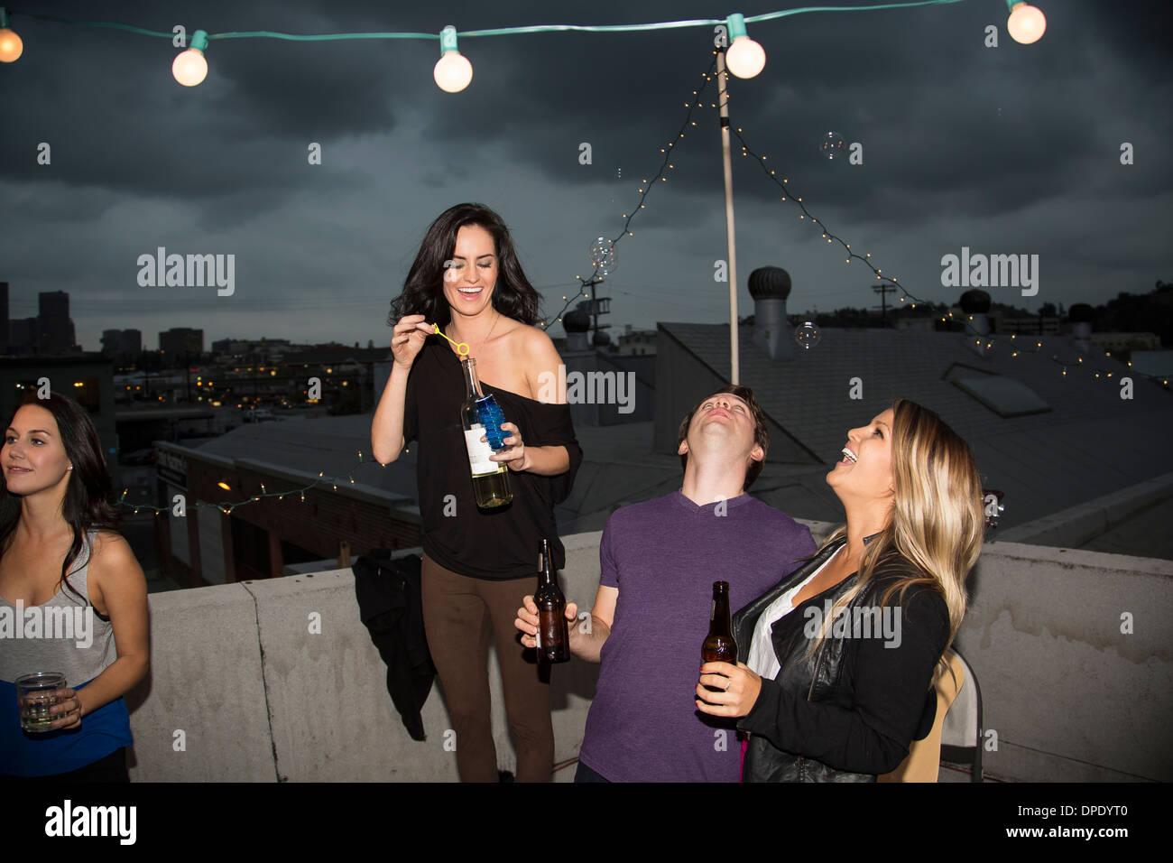 Junge Erwachsene Freunde Seifenblasen auf Party auf dem Dach Stockbild