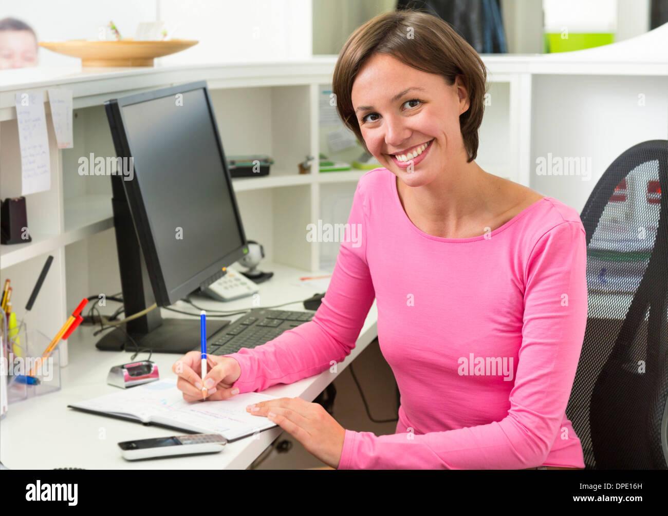 Empfangsdame schreiben am Schreibtisch Stockbild