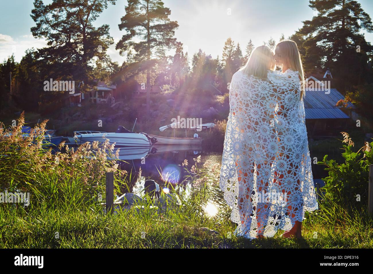 Zwei junge Erwachsene weibliche Freunde in Decke gehüllt, Hotels, Schweden Stockbild