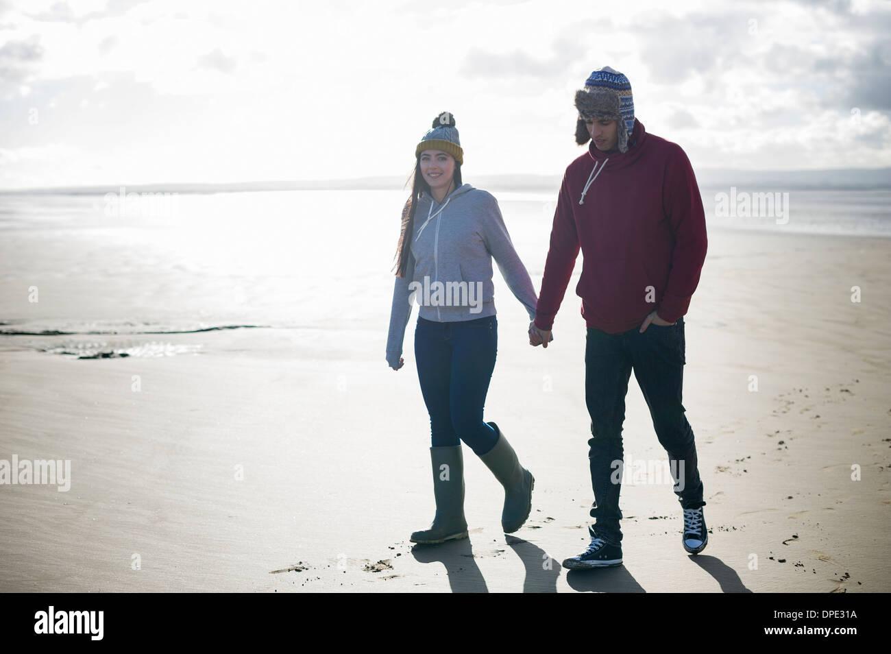 Junges Paar zu Fuß am Strand, Brean Sands, Somerset, England Stockbild
