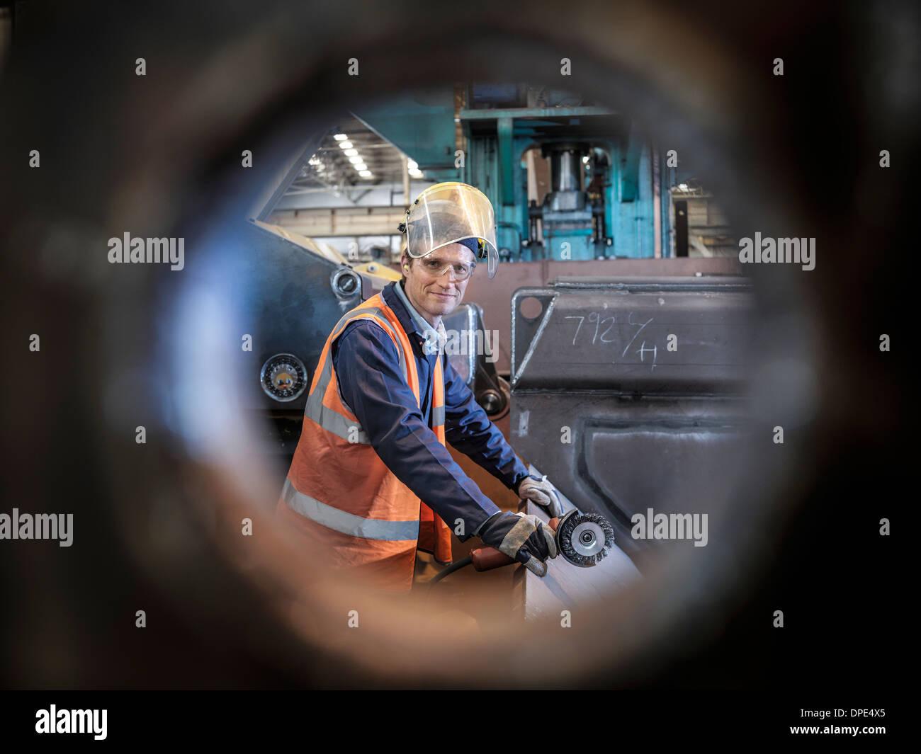 Ingenieur-Porträt im Werk angesehen durch Bohrung in Stahl Stockbild