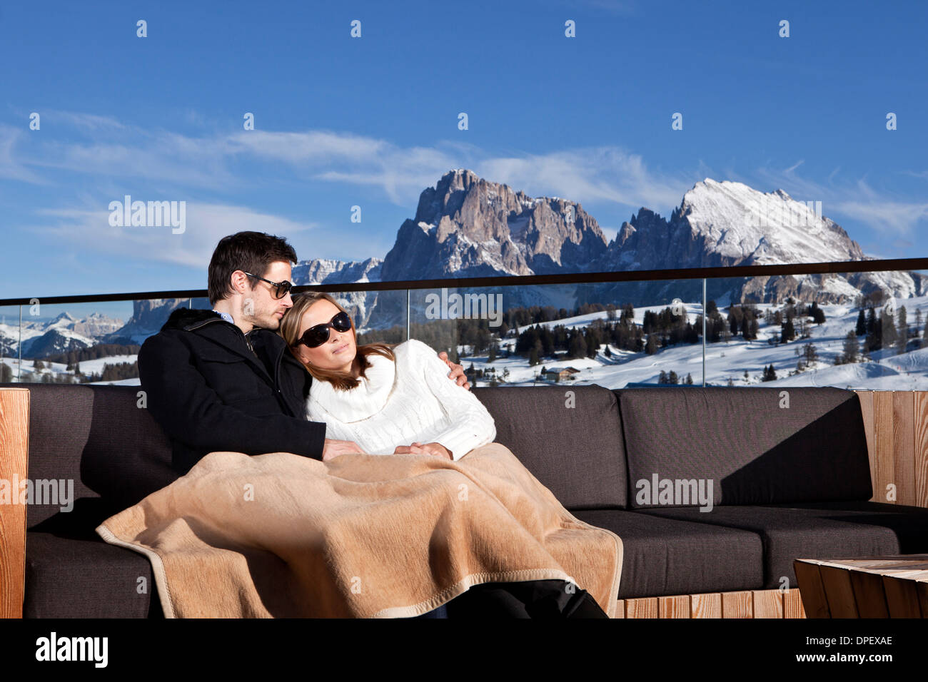Mann und Frau sitzen auf einer Couch im Freien, Seiser Alm, Südtirol, Italien Stockbild