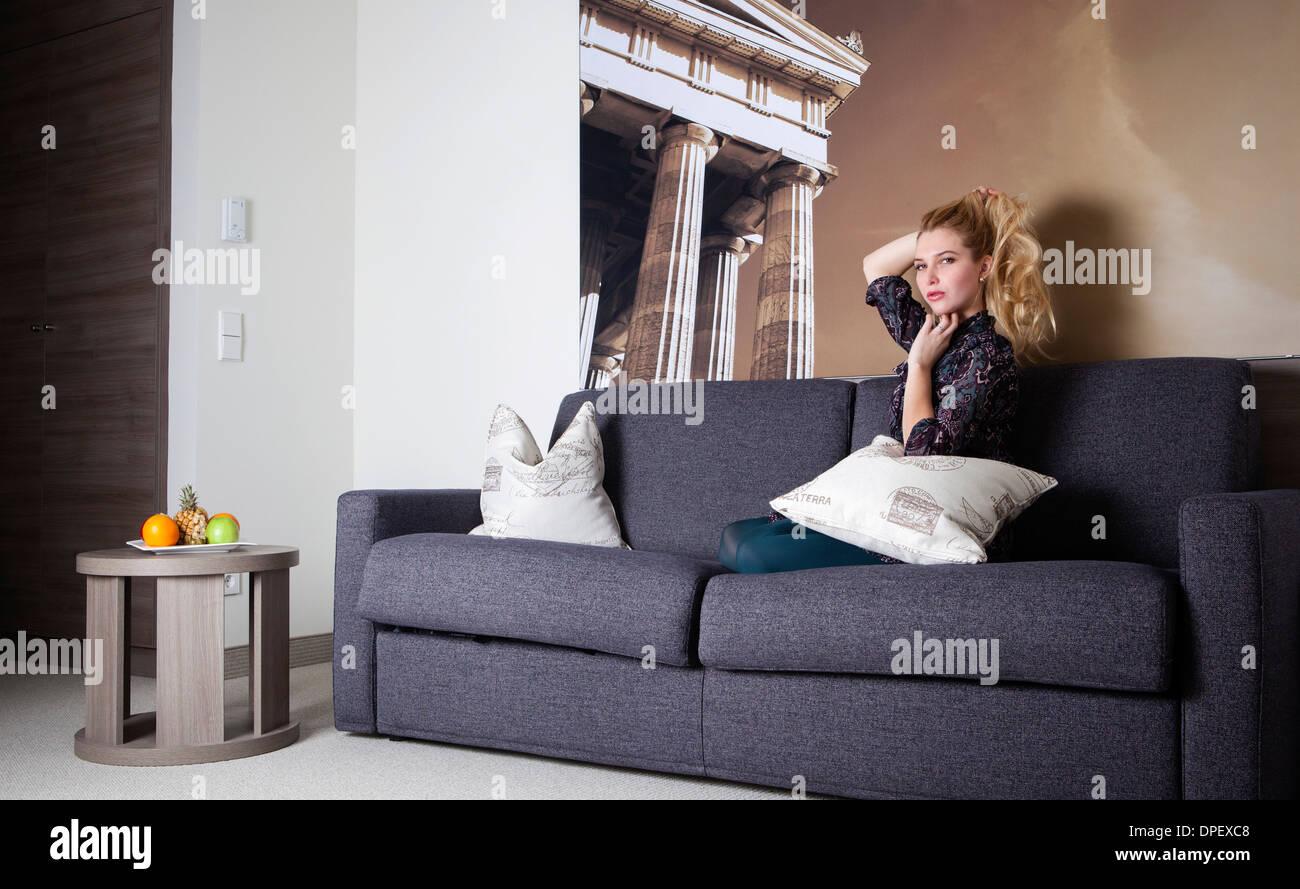 Frau sitzt auf einer Couch in einem Hotelzimmer Stockbild
