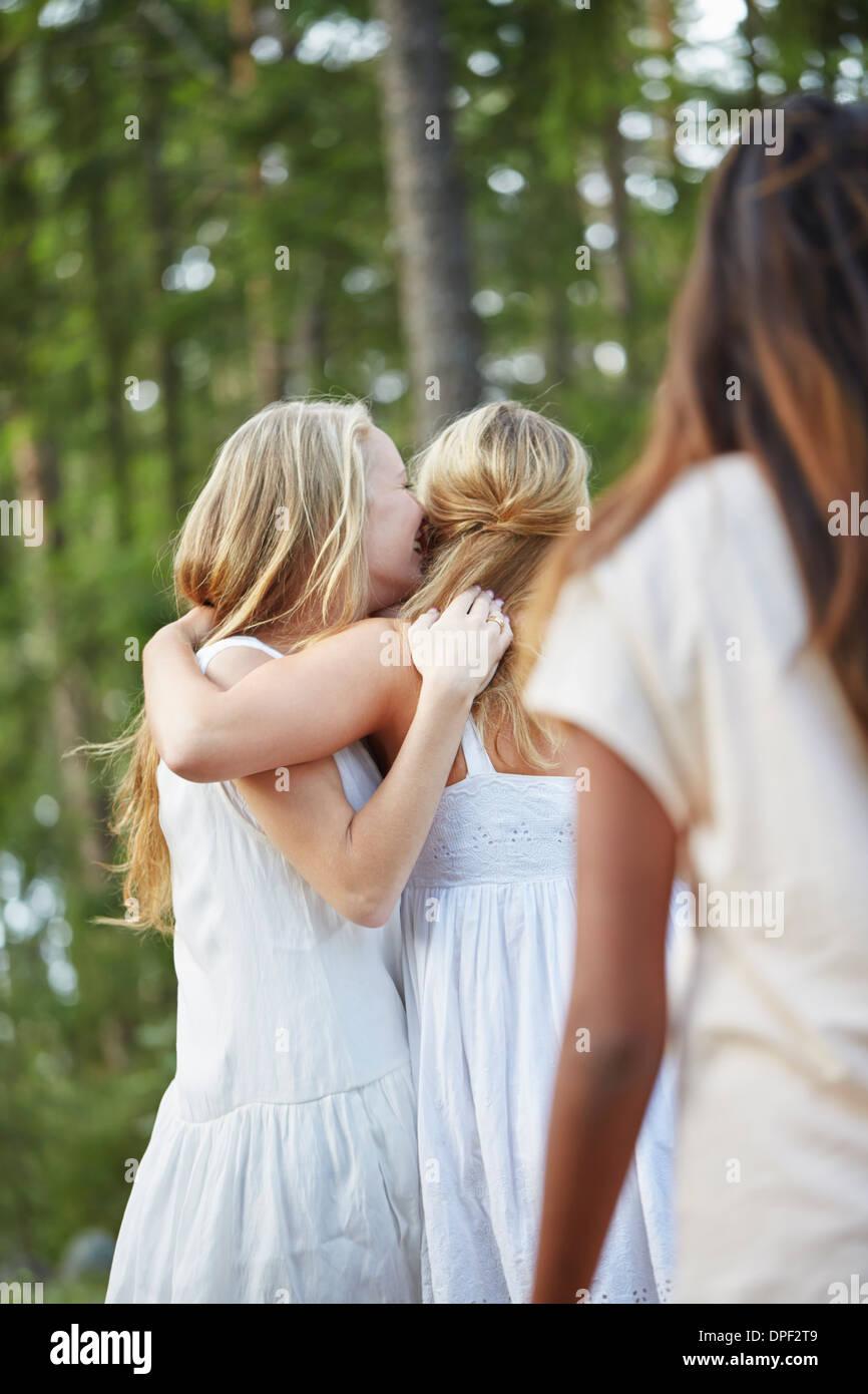 Mädchen im Teenageralter mit Arm umeinander im Wald Stockbild