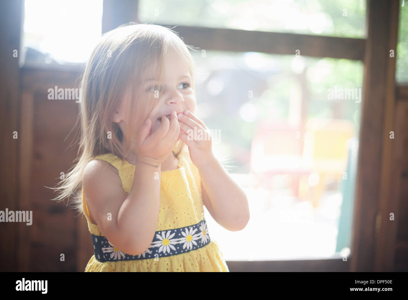 Nahaufnahme eines weiblichen Kleinkind mit Händen über Mund Stockbild