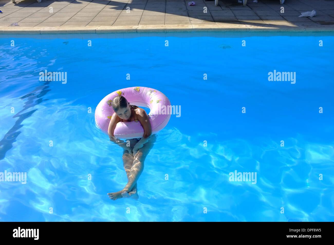 Eine 10 Jahre alte gedankenverloren in einem Schwimmbad Stockbild
