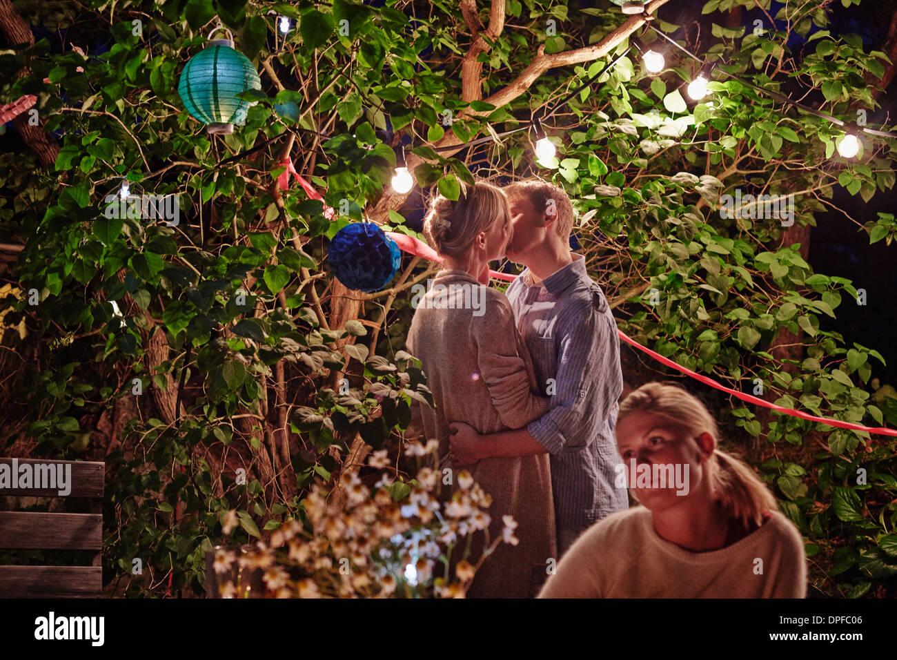 Junges Paar umarmt bei Garten-Party in der Nacht Stockbild