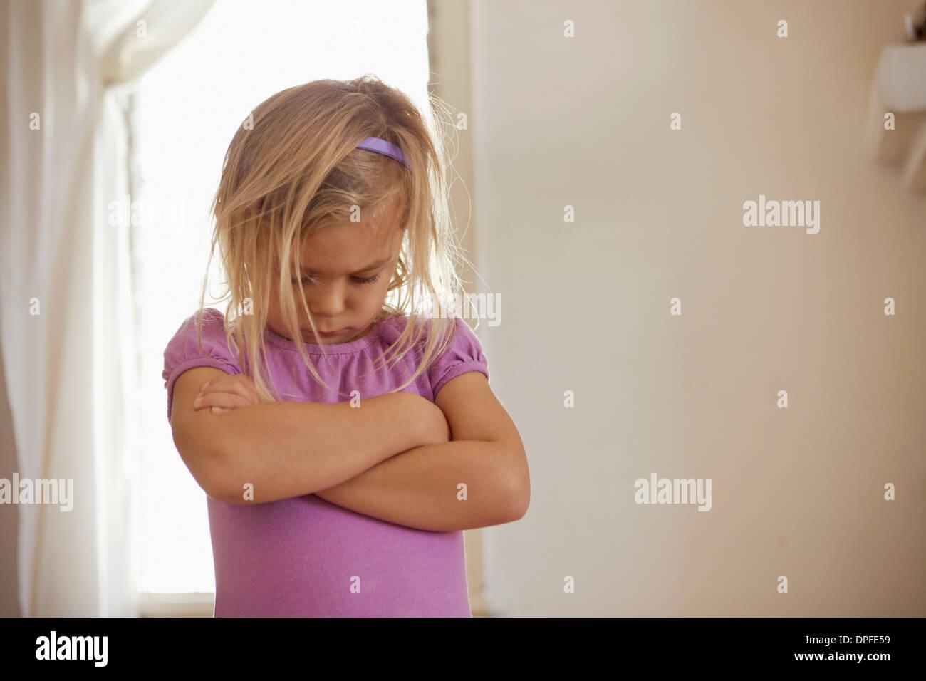 Junges Mädchen mit Kopf und Armen gefaltet mit Wutanfall Stockbild