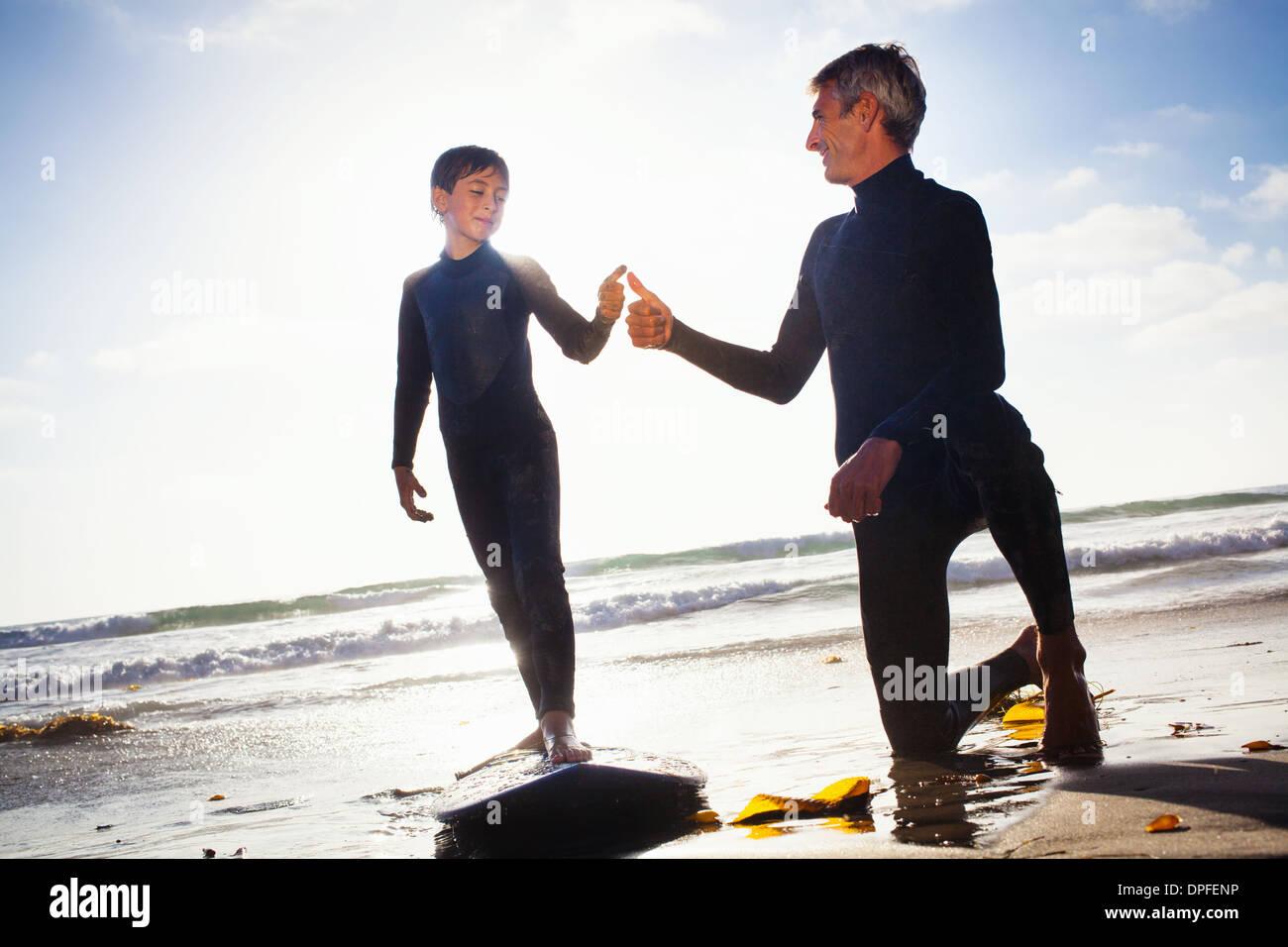 Vater und Sohn mit Surfbrett am Strand, Encinitas, Kalifornien, USA Stockbild