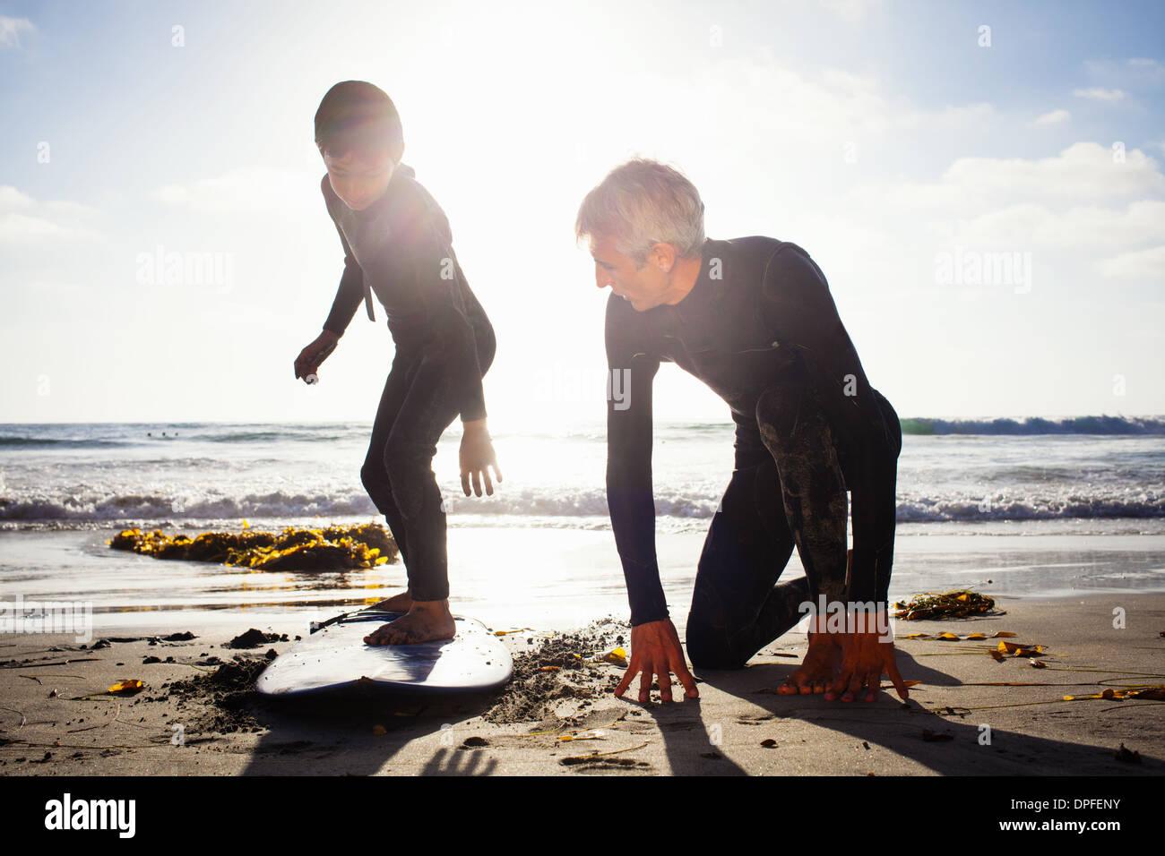 Vater und Sohn üben mit Surfbrett am Strand, Encinitas, Kalifornien, USA Stockbild
