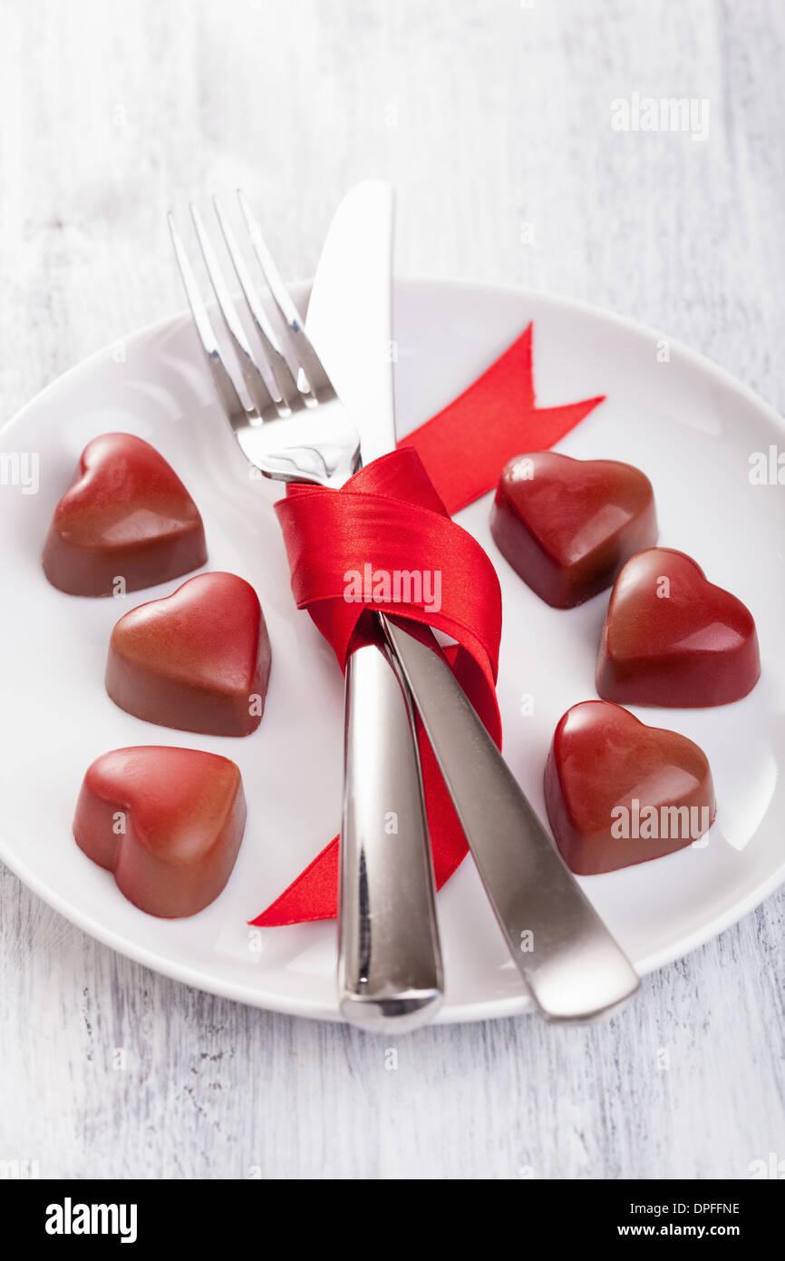Schokoladenherzen und Besteck auf Platte für Valentines Stockfoto
