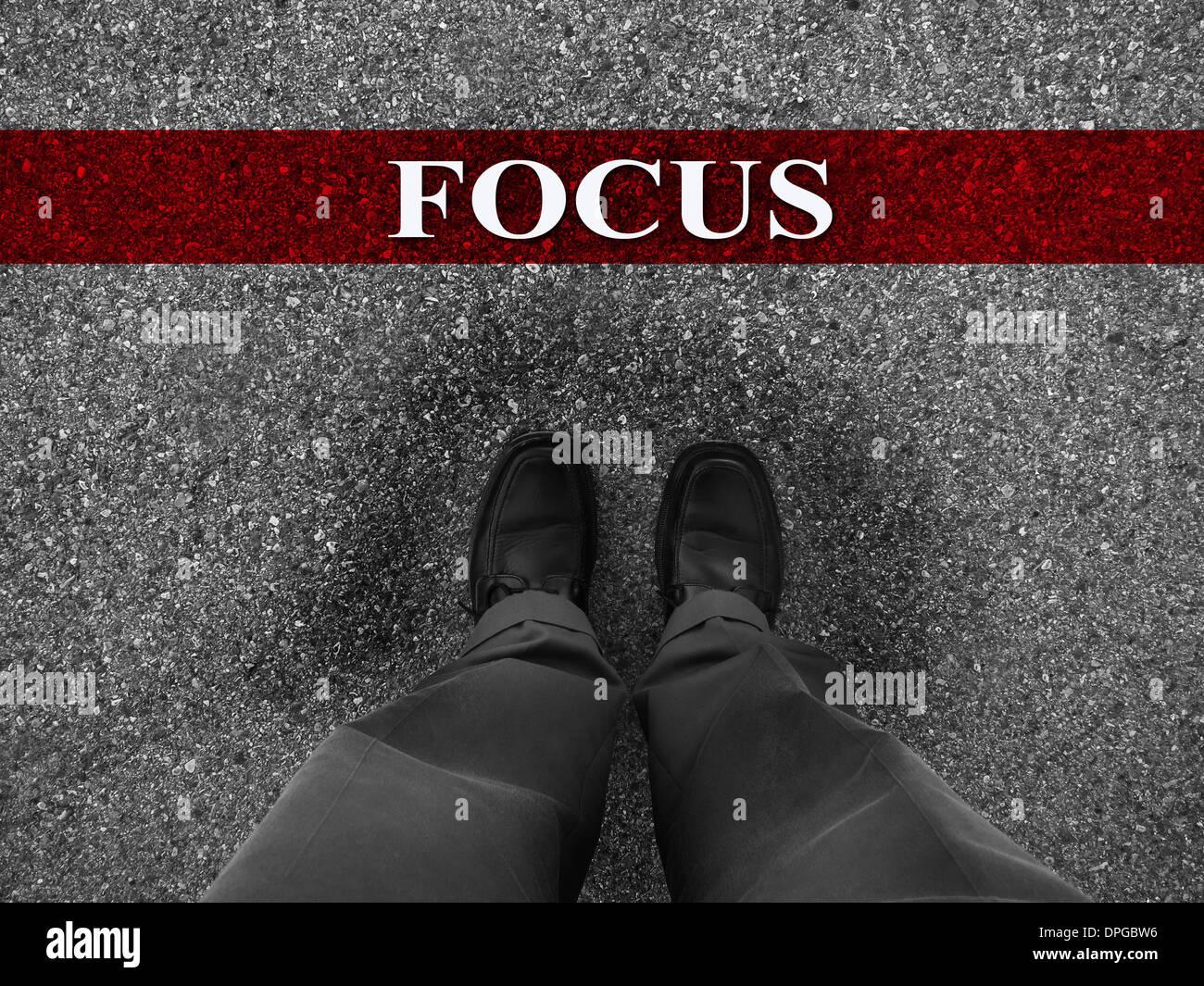 Geschäftsmann, stehend auf Asphalt Startlinie mit Motivation Wort des Fokus Stockbild