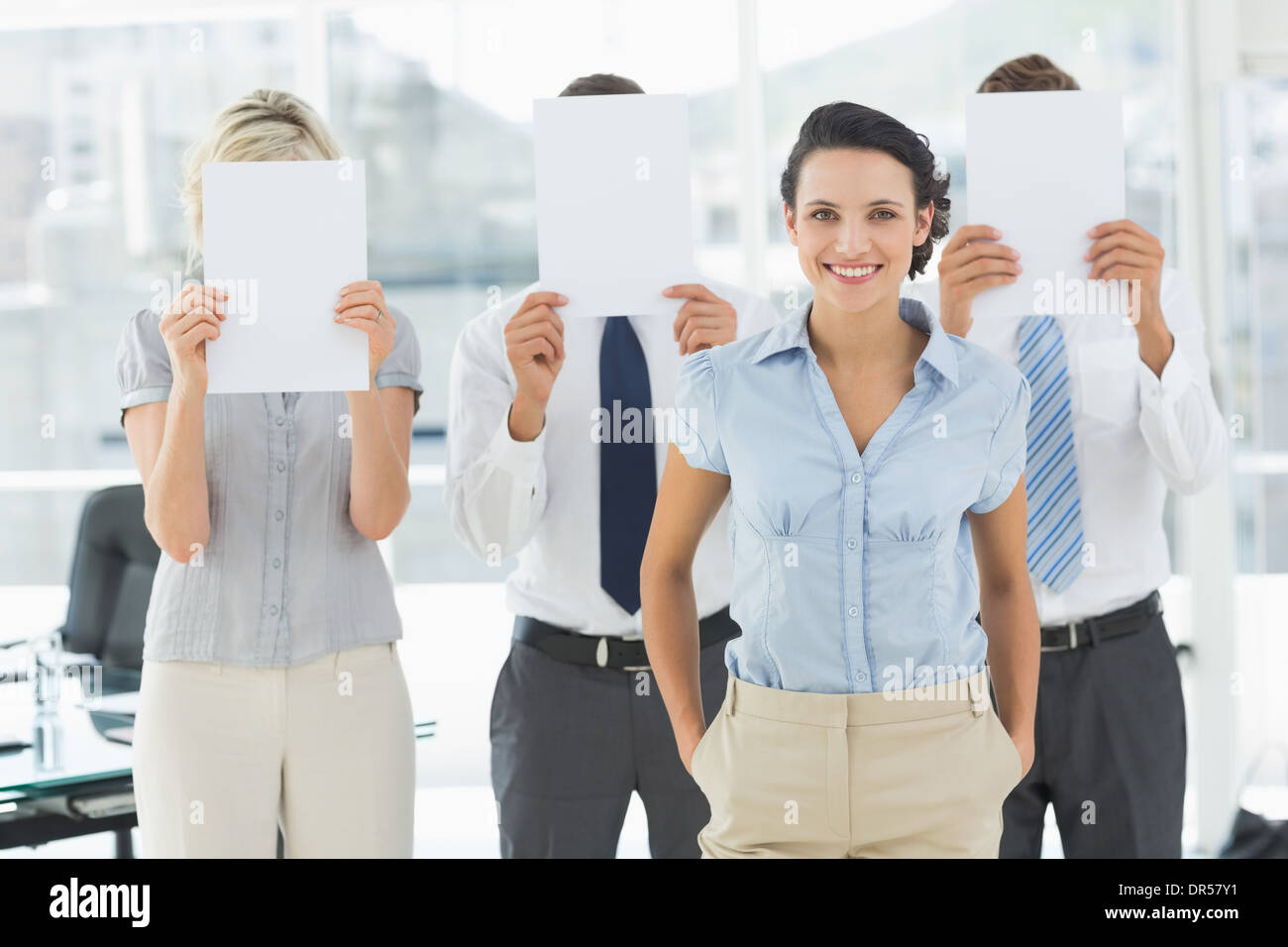 Geschäftsfrau mit Kollegen halten Blankopapier vor Gesichtern Stockfoto