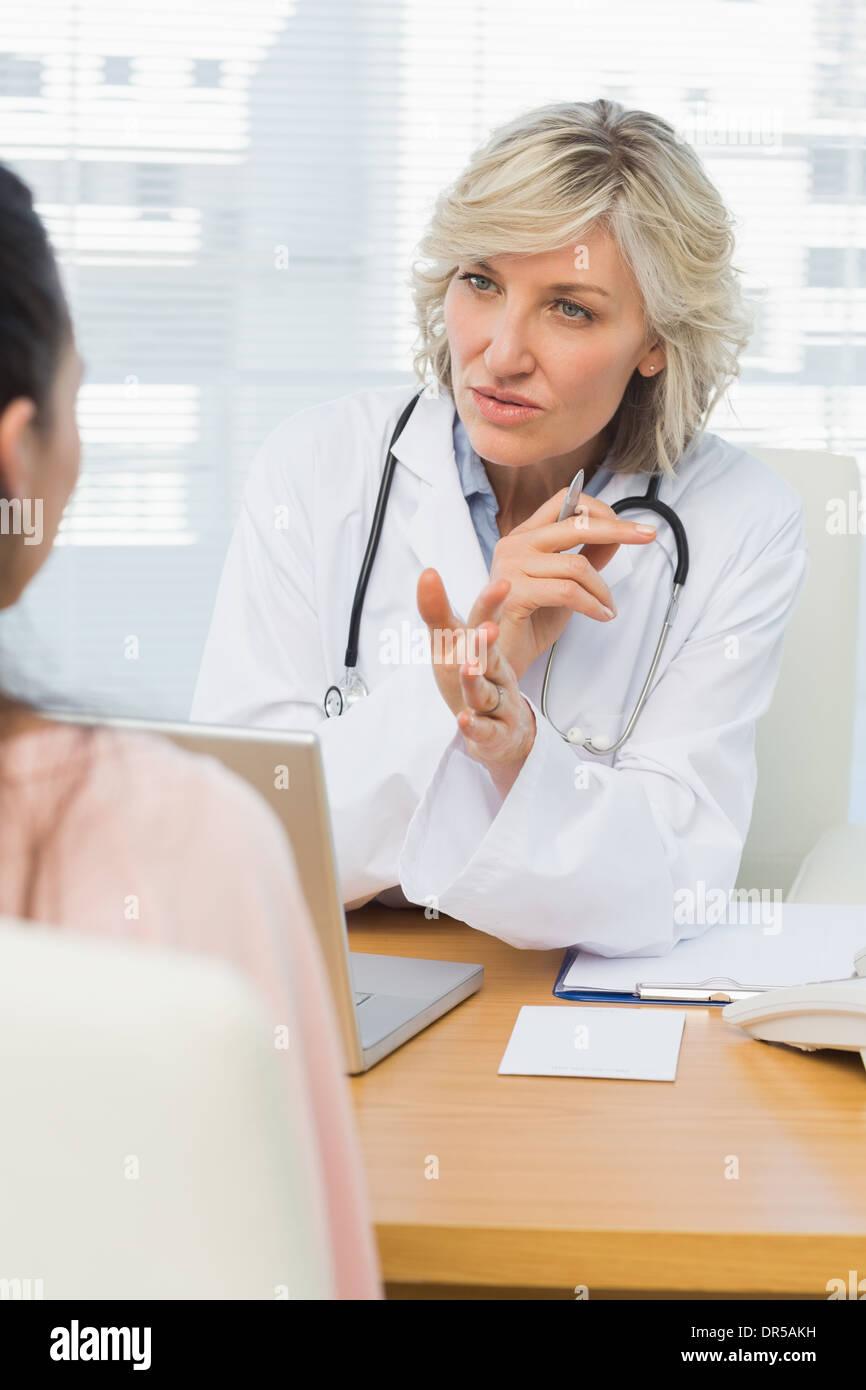Ärztin, die Patienten mit Konzentration zuzuhören Stockbild