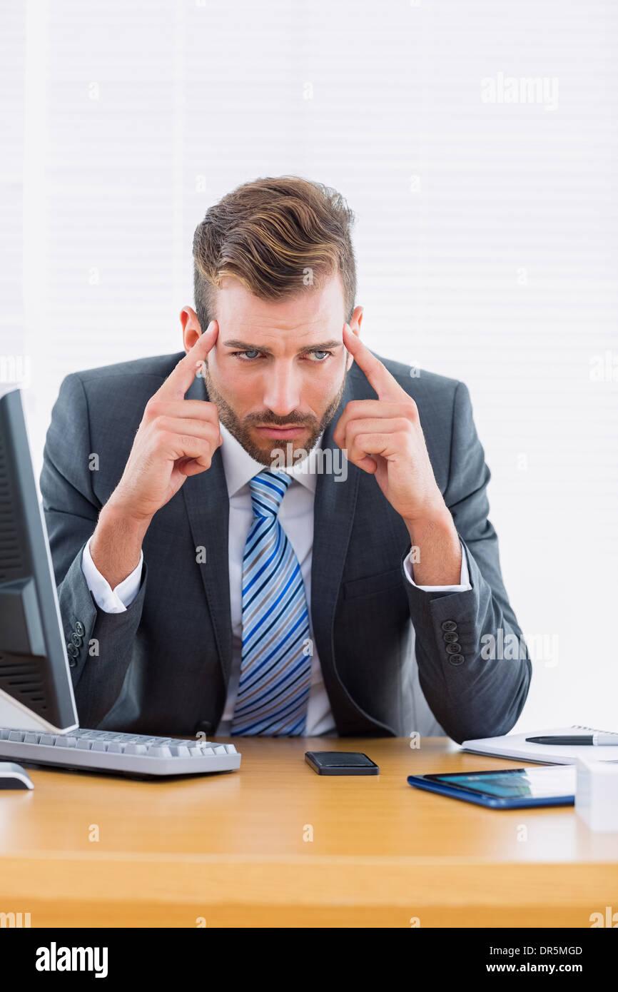 Geschäftsmann mit starken Kopfschmerzen an Schreibtisch Stockbild