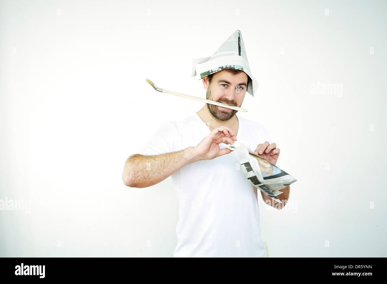 Mann mit Zeitung Hut Papierfaltens, München, Bayern, Deutschland Stockbild