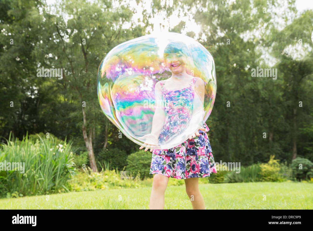 Vater und Tochter spielen mit großen Luftblasen im Hinterhof Stockfoto