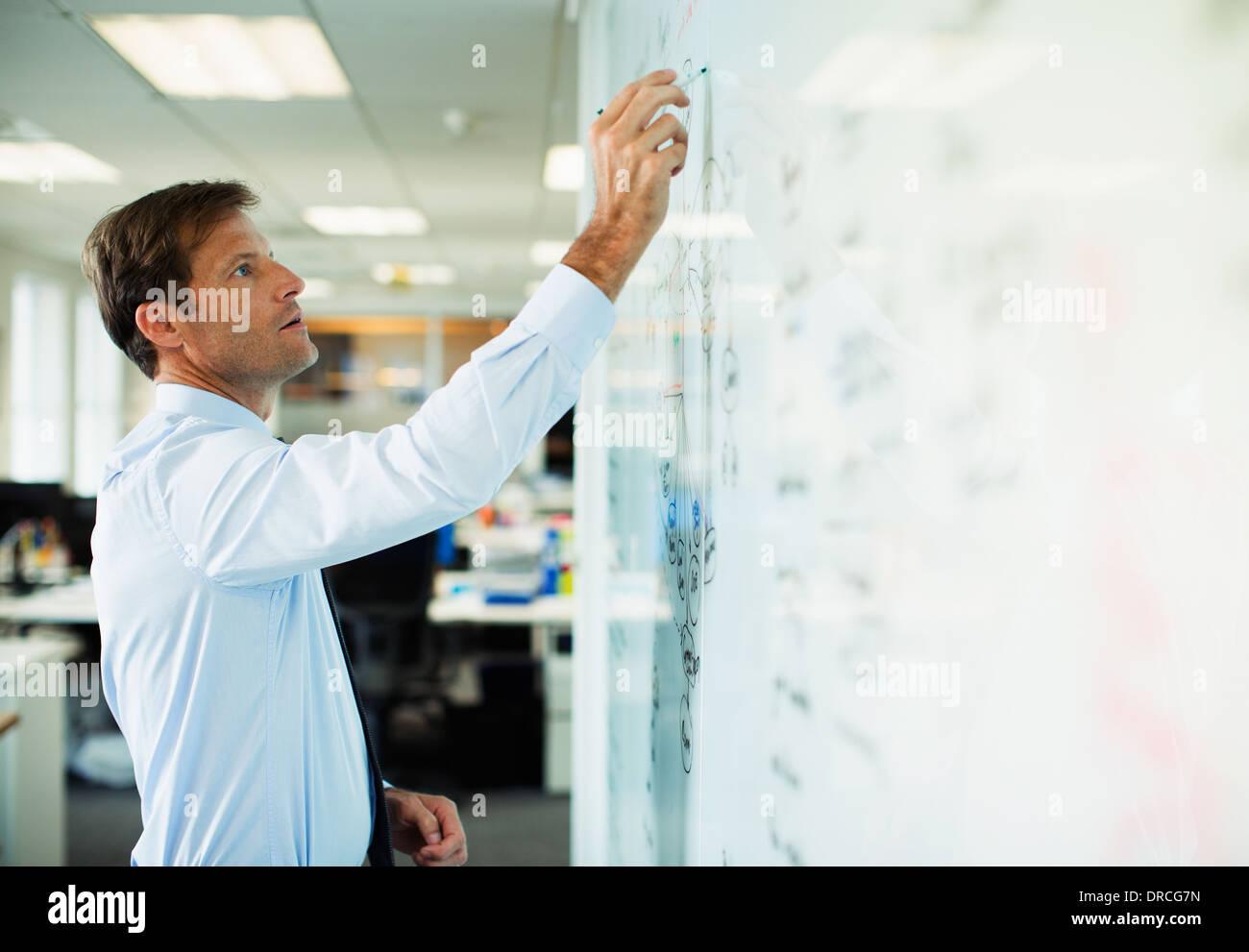 Geschäftsmann am Whiteboard im Büro schreiben Stockbild