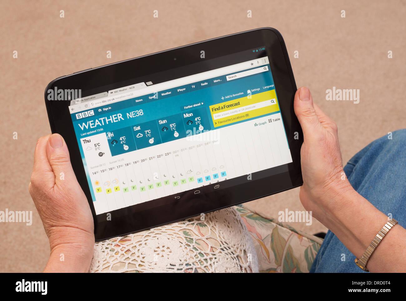 Frau liest UK Wettervorhersage mit Google Nexus 10 tablet Stockbild