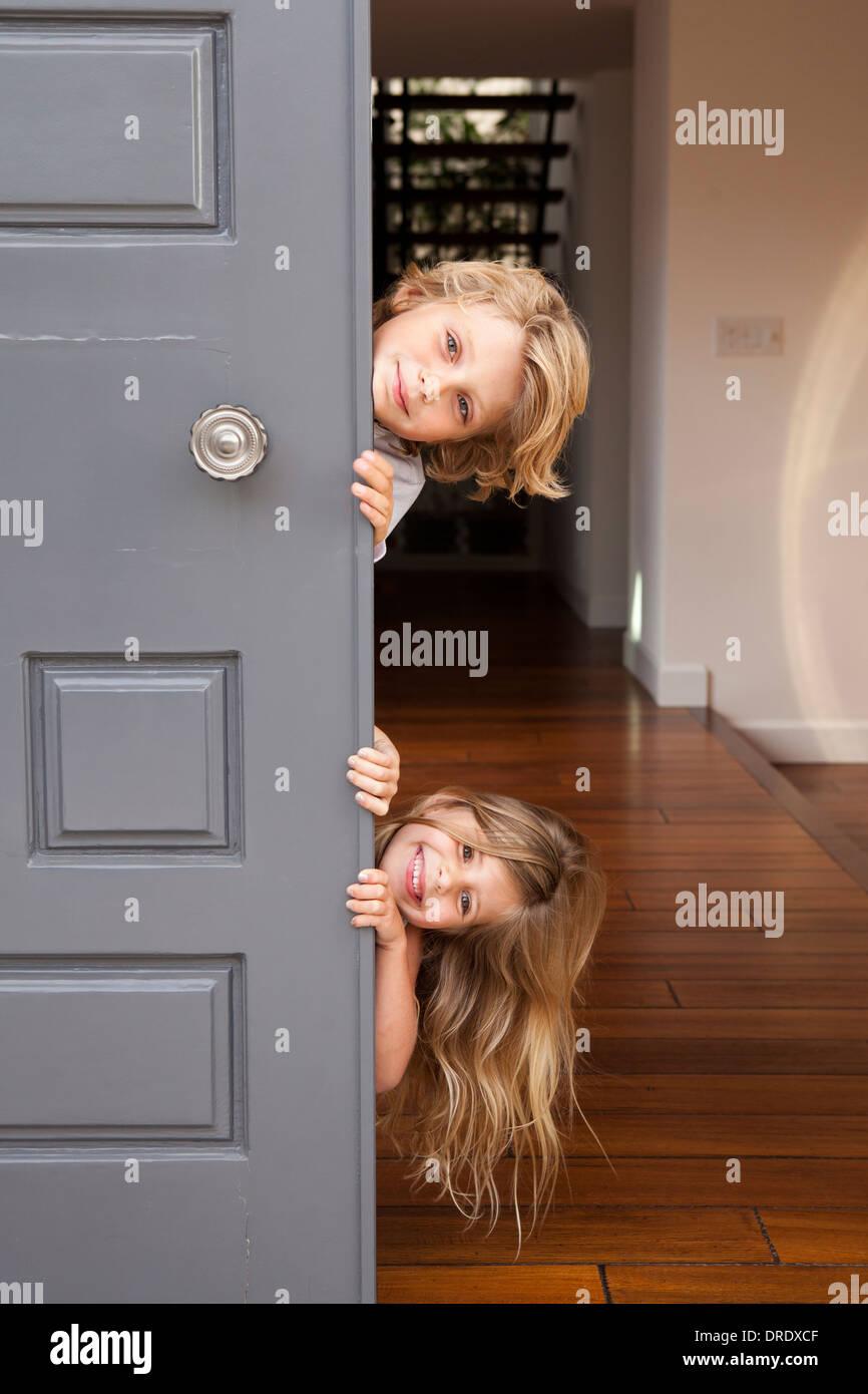 Geschwister, die Tür herausschauen Stockbild