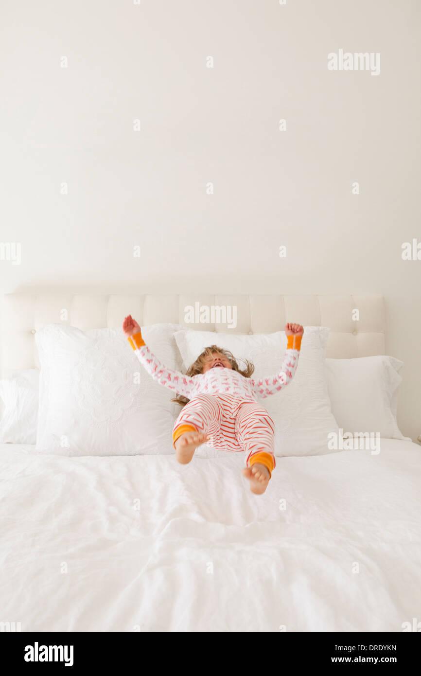 Mädchen in bunten Jammies springen auf Bett Stockbild